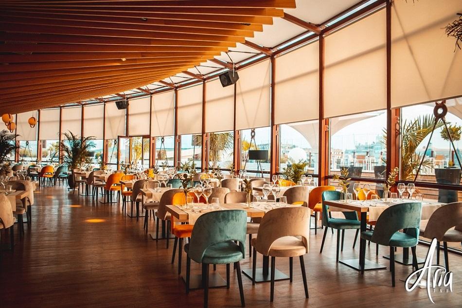 interiorul restaurantului aria tnb, cu o latura din geamuri mari si mese de 4 persoane, cu scaune capitonate, un loc in care poti organiza un eveniment privat