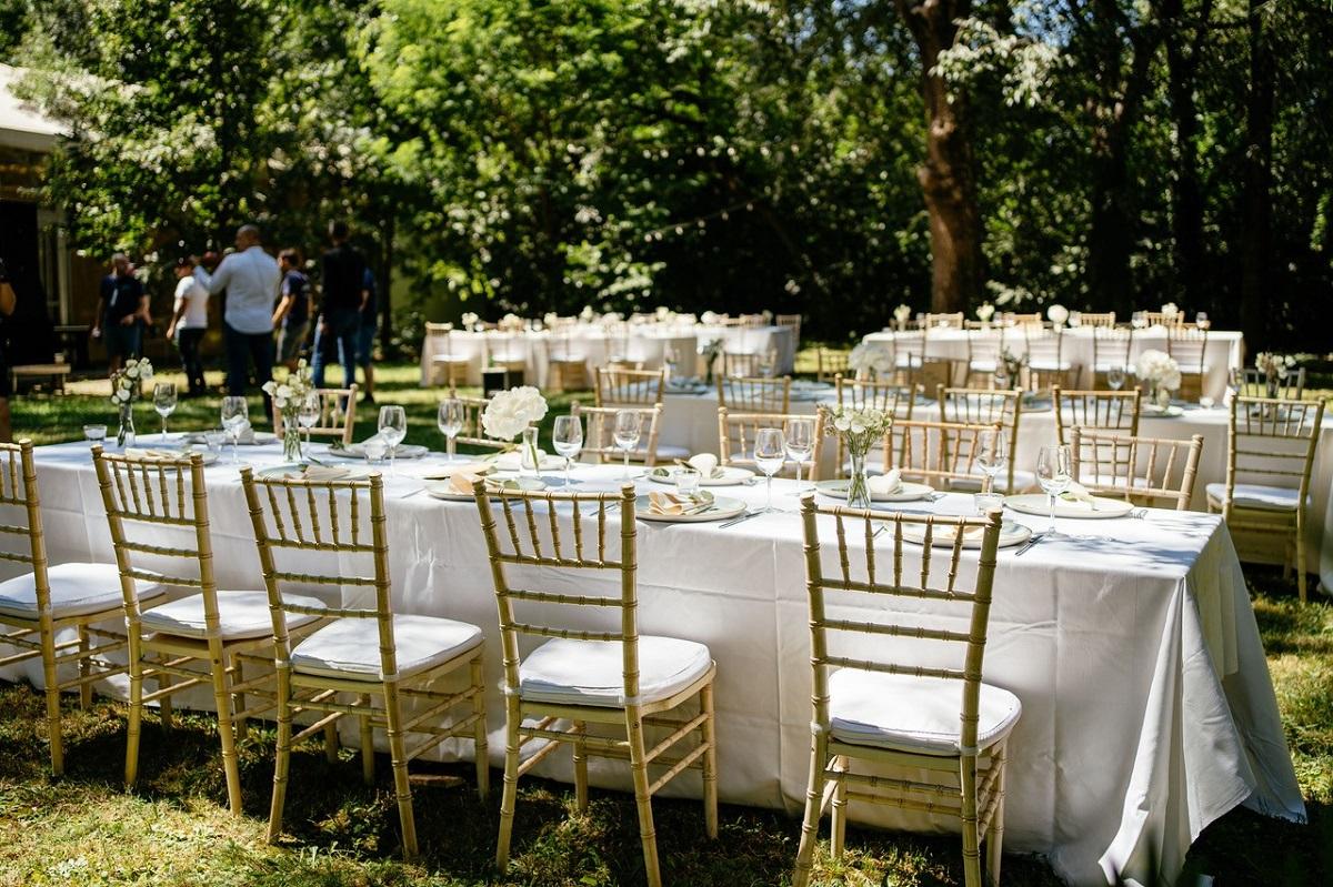 masa decorata ca pentru un eveniment, cu fata de masa alba si ornamente florale, cu scaune de lemn, in gradina verde, la Flavours in the Garden