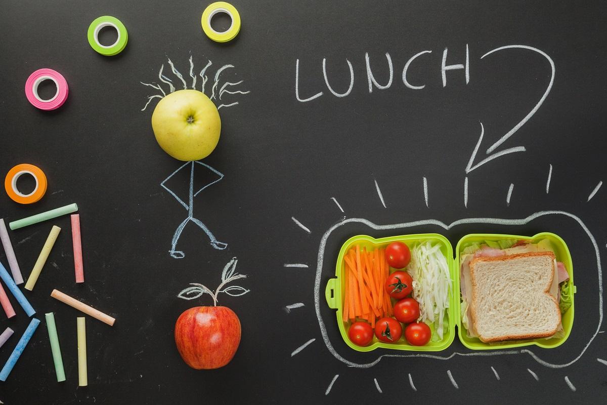 back to school mâncare la pachet în caserola verde, cu legume si frcute, asezate pe o tablă neagră desenată cu cretă si omulet făcut din fructe