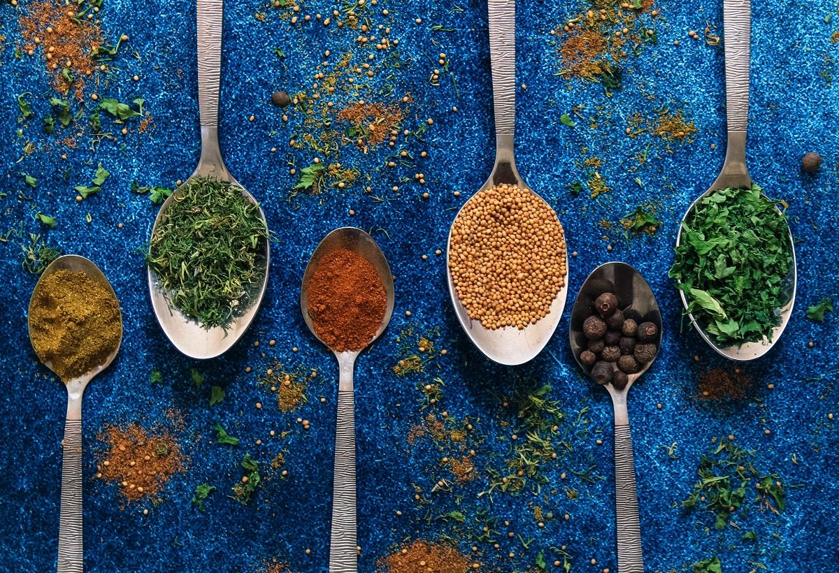 mai multe tipuri de condimente orientale colorate asezate fiecare in linguri metalice, pe funda l albastru