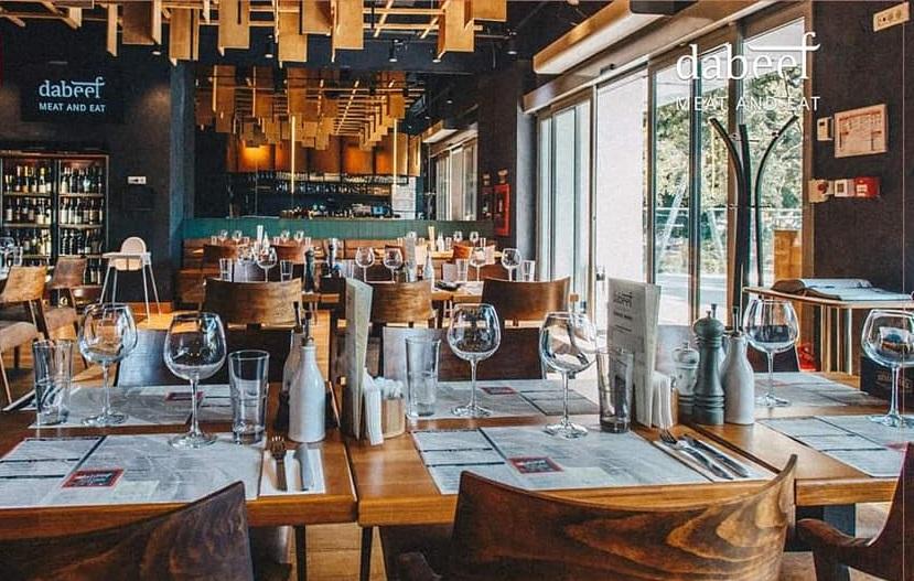 rand de mese din lemn, cu pahare si vesela, in restaurant dabeef, cu pereti negri si tavan cu ornamente din lemn