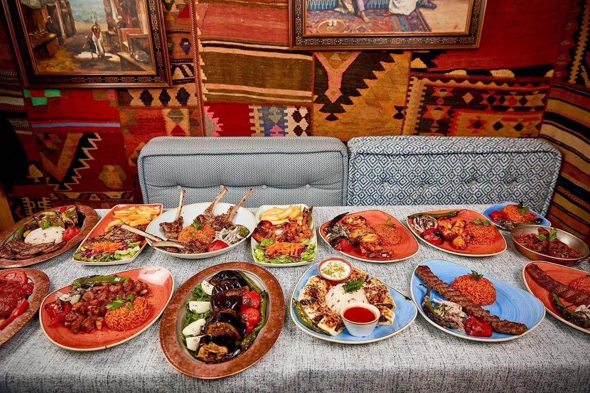 masa intinsa plina cu farfurii cu multe preparate turcesti, in fata unei canapele gri, iar pe perete covoare turcesti, la restaurant divan din floreasca