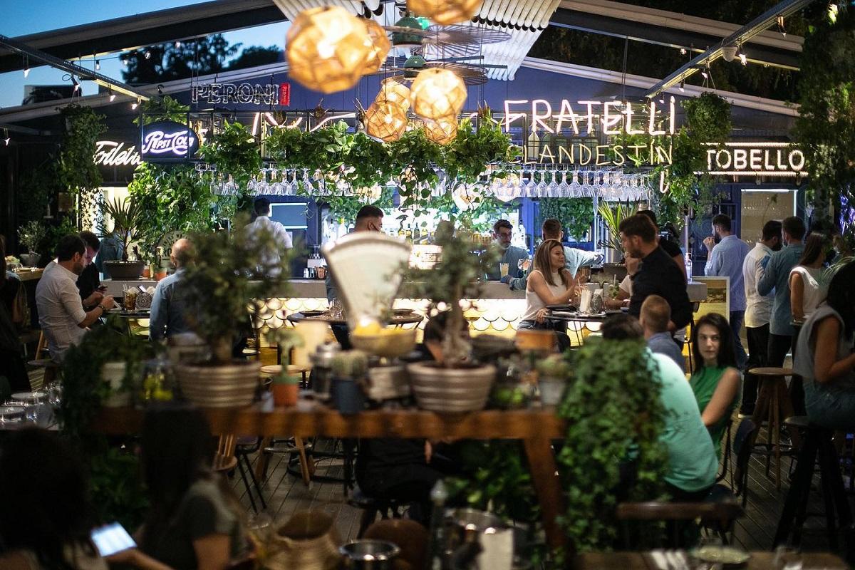imagine de ansamblu de la terasa fratelli herăstrău, cu multe plante, corpuri decortive luminoasre si mese in fundal, terasă cu muzică live