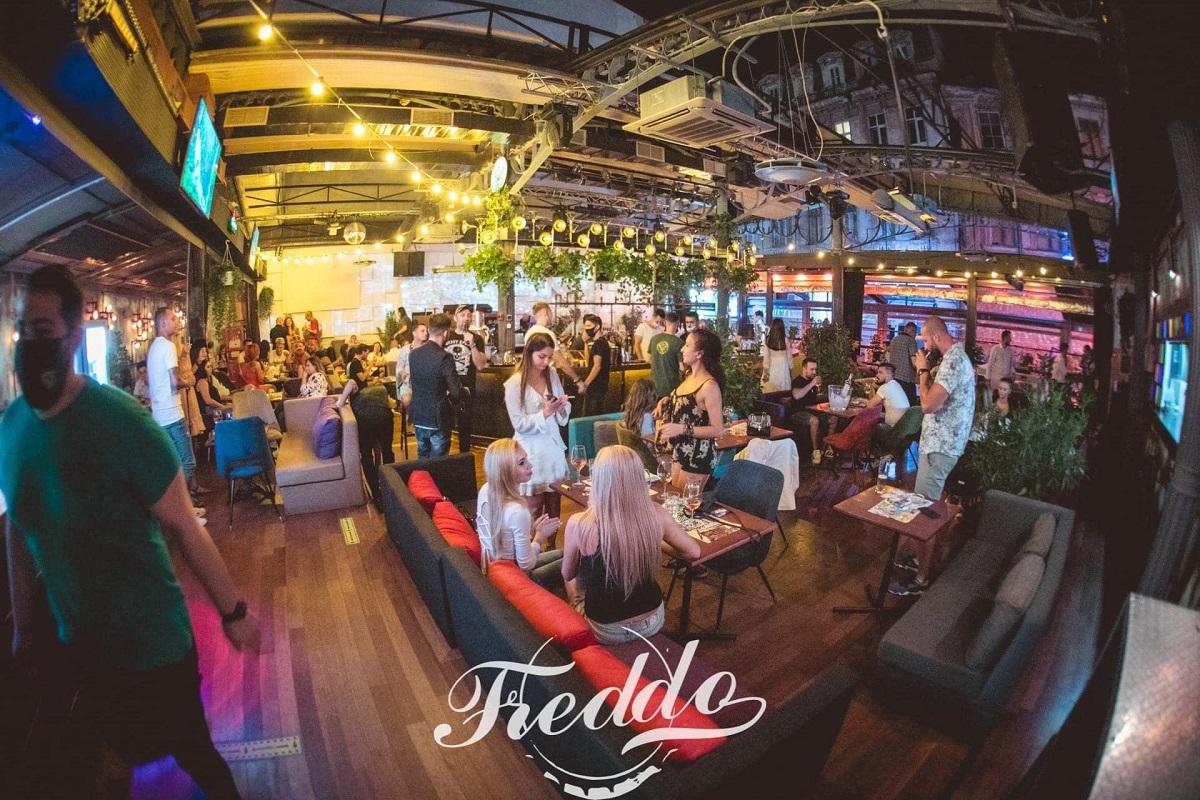 imagine de ansamblu din freddo bar & lounge bucuresti, cu oameni la masa si in picioare si beculte luminoase, la terasă cu muzică live în București
