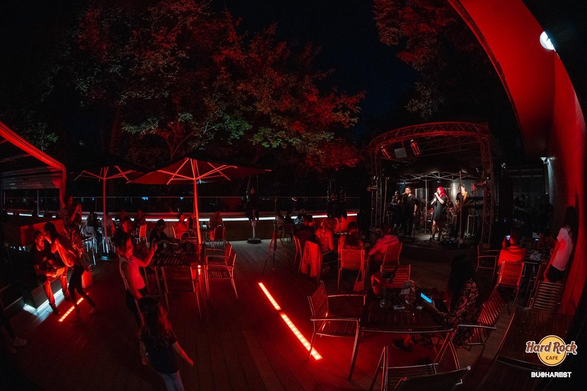 hard rock cafe noaptea, cu oameni la mesele luminate cu beculete rosii, ascultand la terasă muzică live