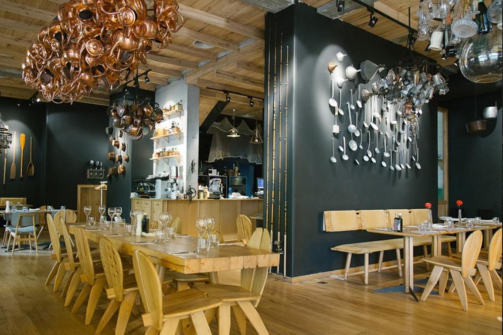 restaurantul sardin la interior, cu pereti negri, mese si scaune din lemn, corpuri de iluminat din strachini aramii si pereti decorati cu polonice