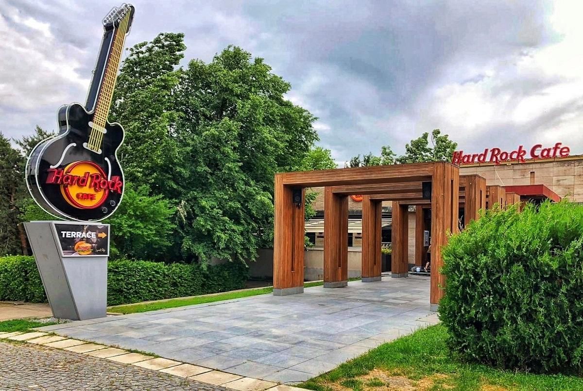 intrarea la restaurant hard rock cafe, cu o chitara mare luminoasa la intrare si pergola de lemn pe aleea de beton
