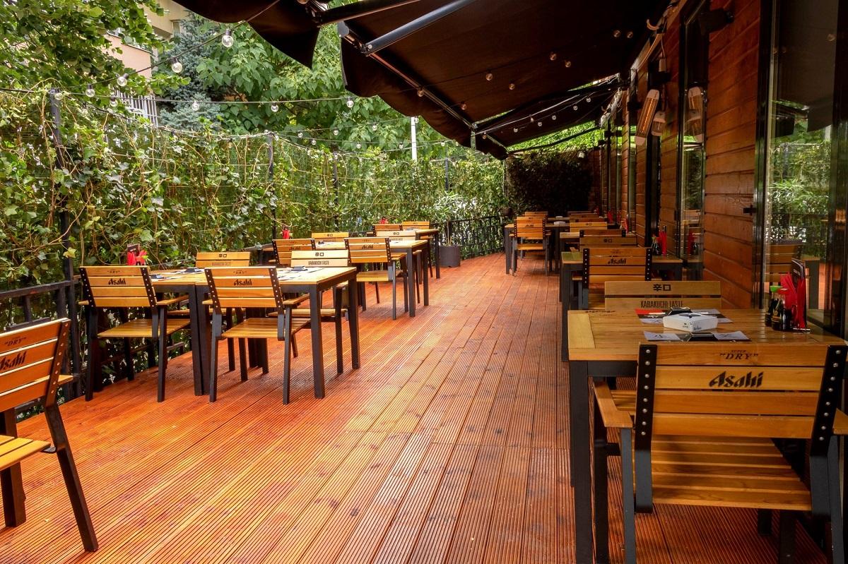imagine de ansamblu de pe terasa kanpai bistro din floreasca, cu podea de lemn si mese si scaune din fier forjat cu lemn, iar pe lateral multa verdeata,la kanpai bistro din floreasca