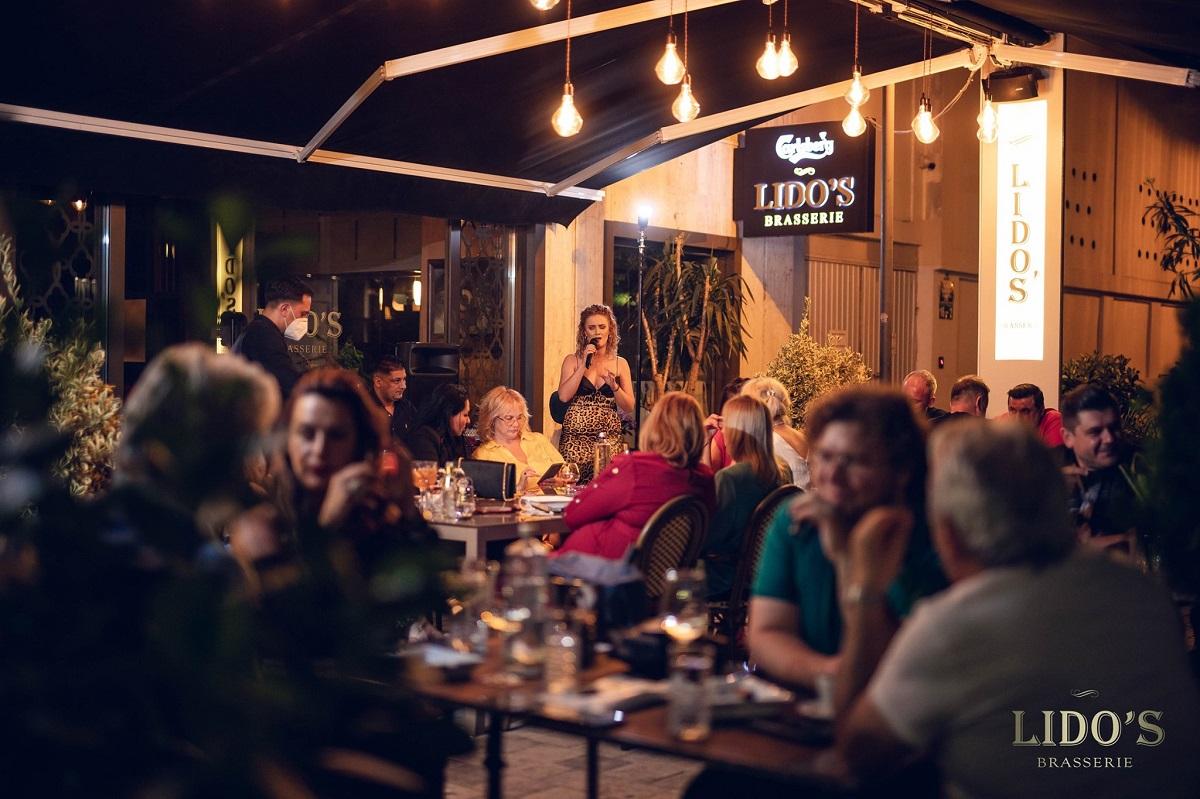seara pe terasa la lidso brasserie, cu oameni stand la masa si o femeie cantand in fundal la microfon , muzică live