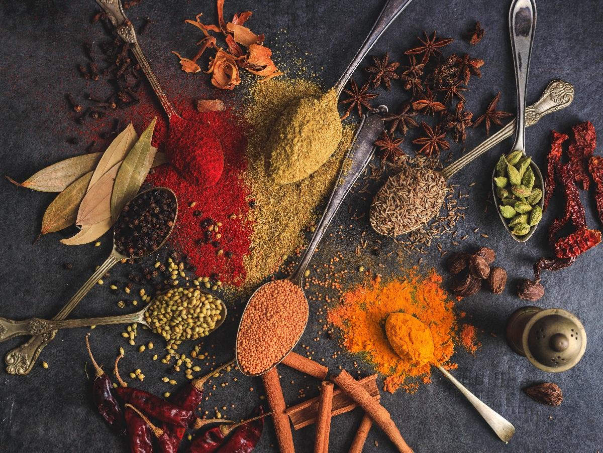 Amestec de condimente si mirodenii, presarate pe o masa neagra sau in linguri metalice, in culori de rosu, portocaliu, galben si negru