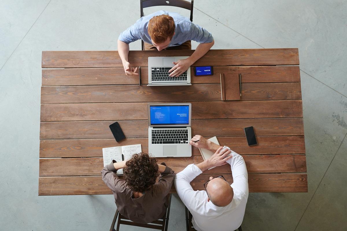 oameni de afaceri fotografiati de sus, la birou, cu laptop in fata, imagine sugestiva pentru ghid de renegociere