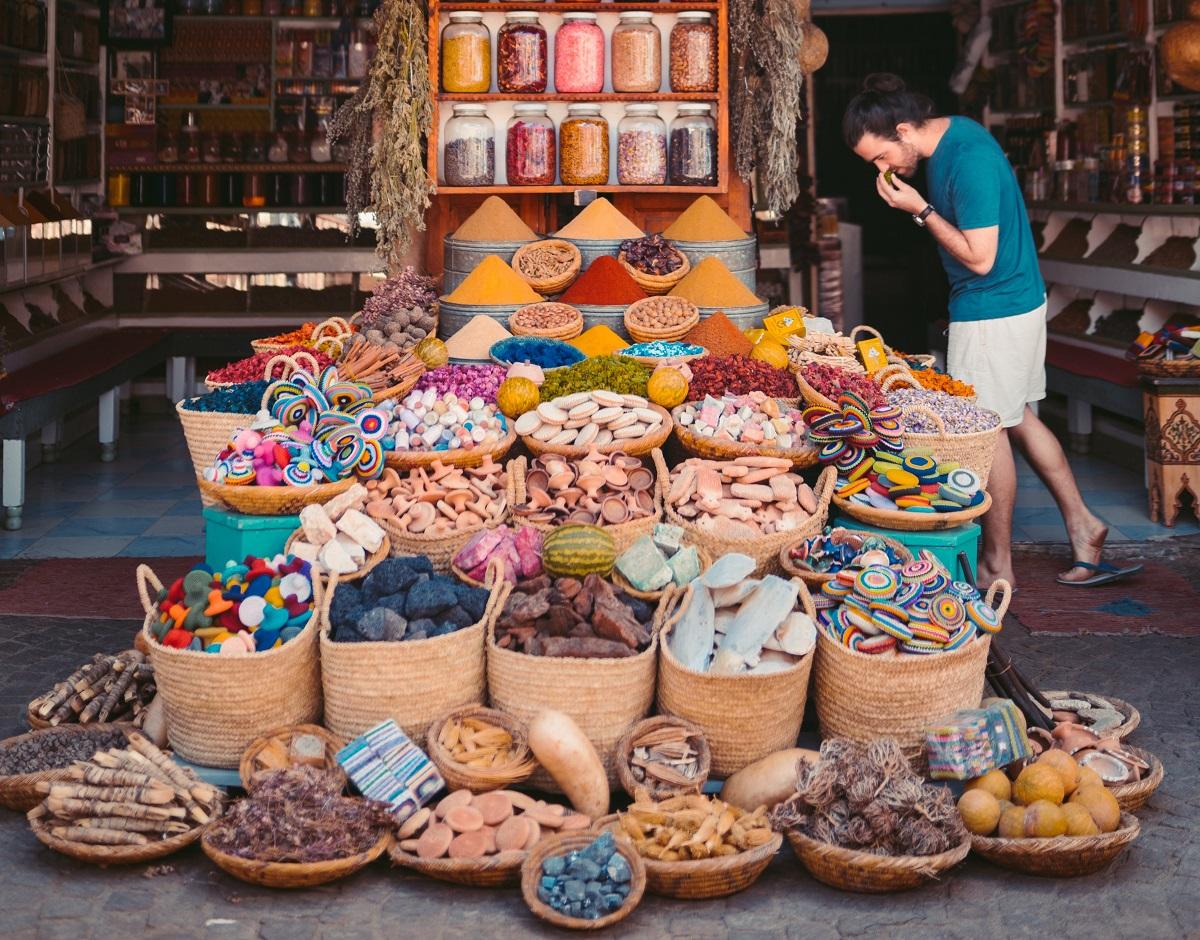 barbat in piata de condimente orientale, la un magazin strada plin cu cosuri cu mirodenii, borcane de condimente si produse artizanale