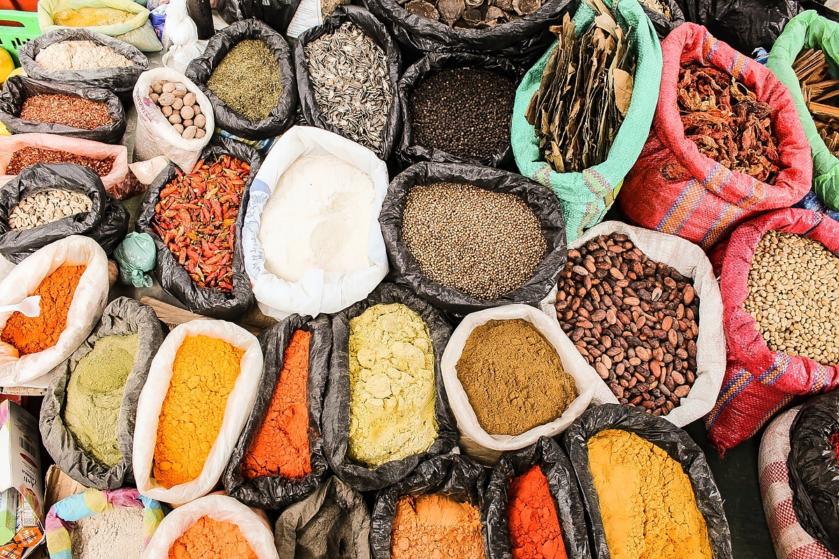 saci cu condimente orientale fotografiati de sus, in culori de galben, alb, portocaliu, maro, negru etc
