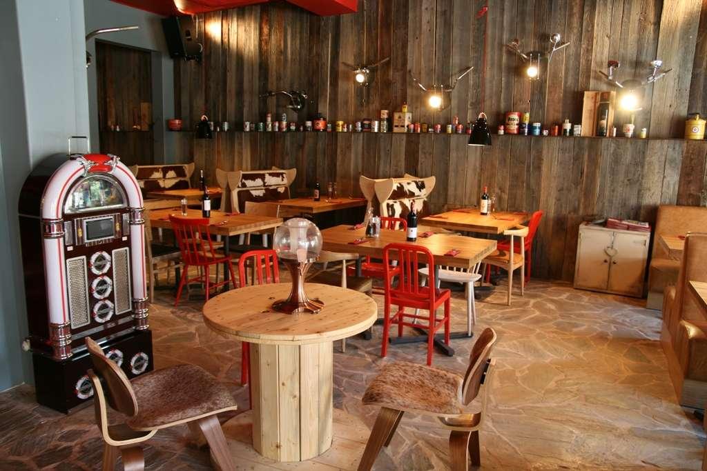 imagine de ansamblu din restaurant red angus steakhpuse la interior, cu pereti din stinghii de lemn, podea de lemn, mese de lemn, scaune cu rosu, si o masa rotunda