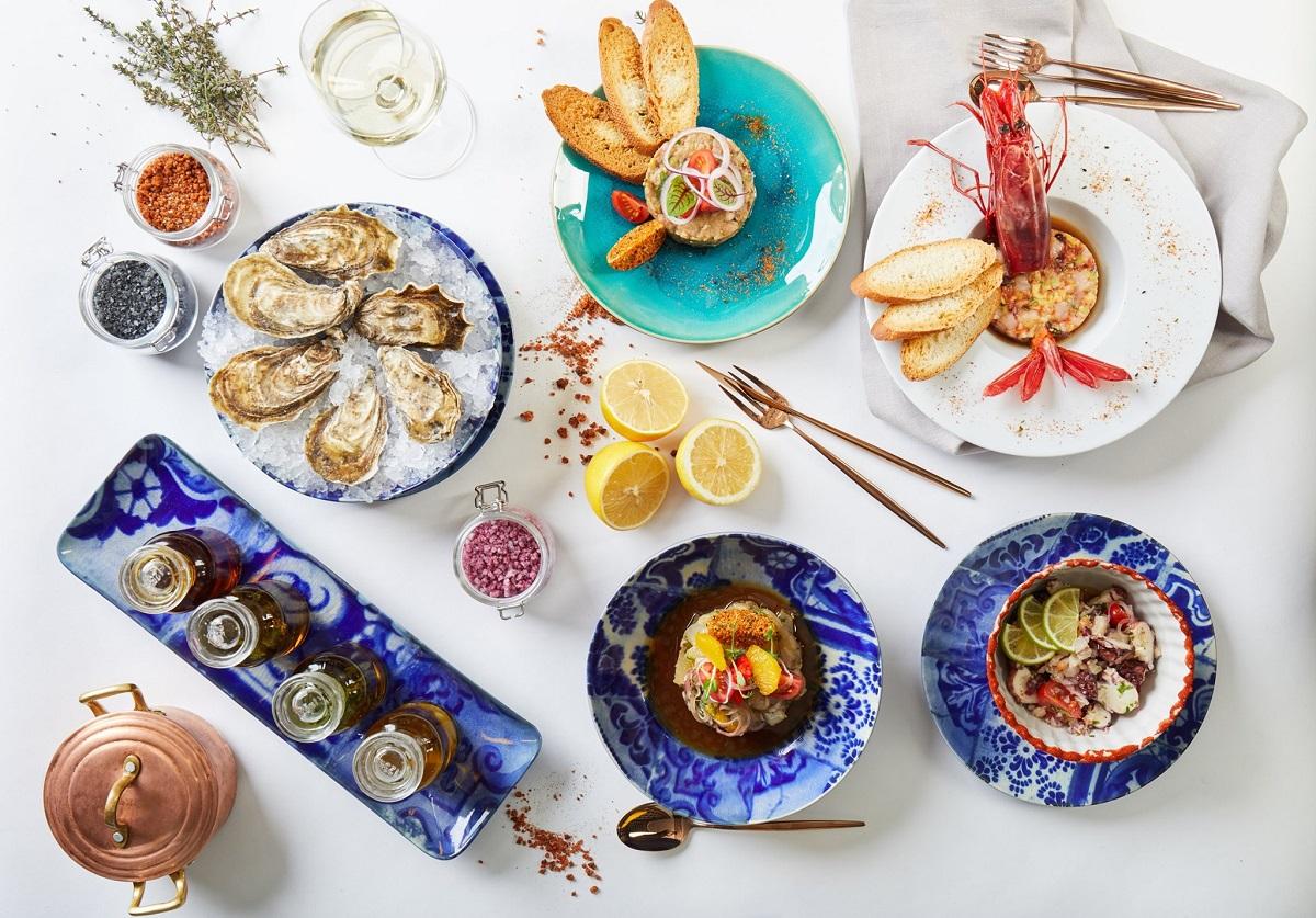 masa fotografiata de sus, cu multe farfurii cu preparate portugheze, in farfurii si boluri albe si albastre, la restaurant dancing lobster din barbu vacarescu