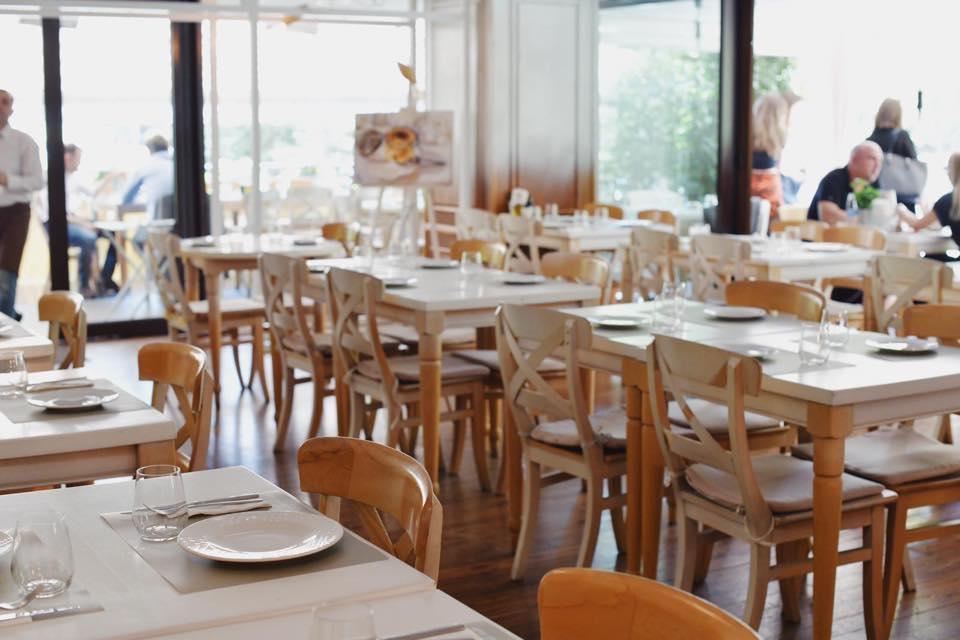 prim plan cu mese asezate la interior in restaurant fior di latte bucurești, cu fete de masa albe si scaune de lemn natur si ferestre mari in fundal