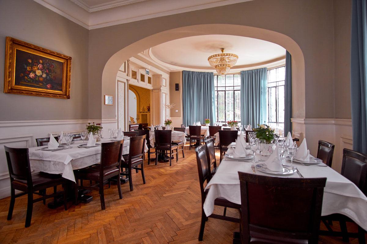 sala de mese de la restaurant zexe sofia in interior, cu parchet de lemn, tavan cu bolta, mese de lemn, ferestre mari in fundal, cu draperii albastre