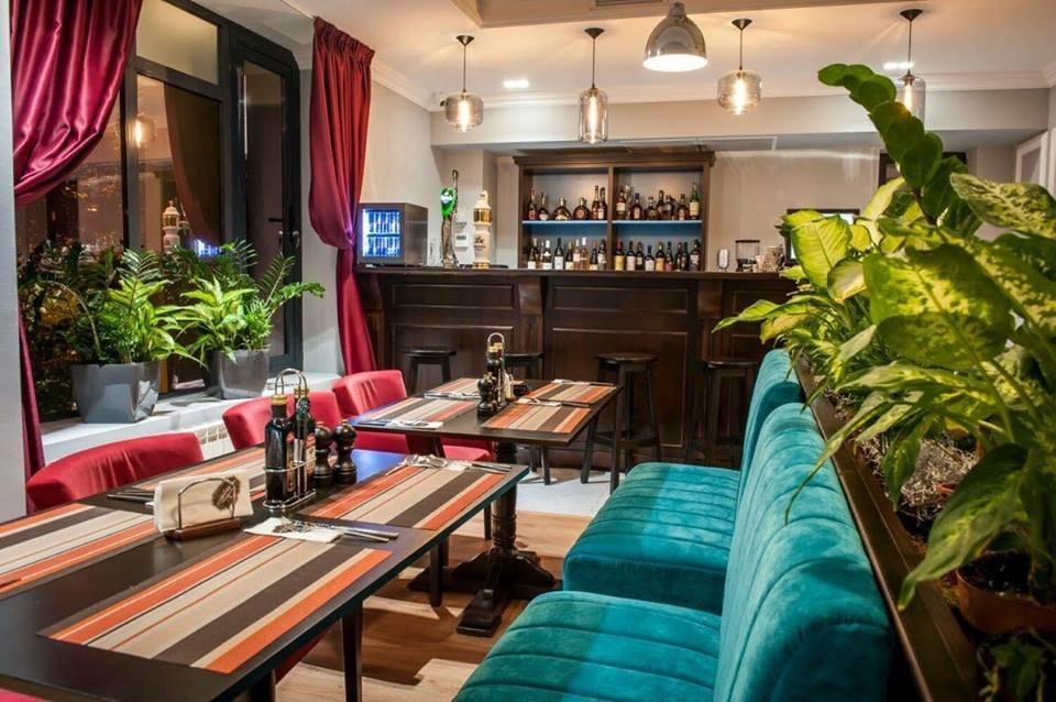 canapele albastre in fata carora stau mese patrare cu dungi colorate iar in fundal un bar cu sticle de bautura la restaurant samuelle în interior