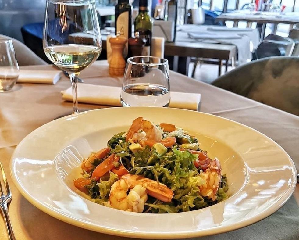 prim plan cu farfurie cu salata verde si creveti si pahare de vin asezate pe o masa la restaurant mozzafiato din floreasca