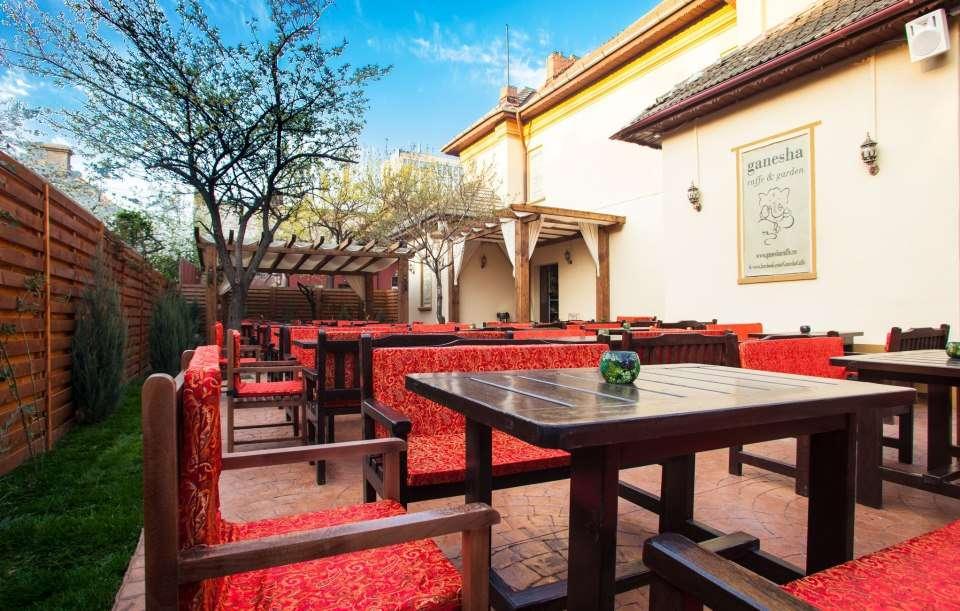 terasa manejata in curtea unei case, cu mese de lemn inchis la culoare si canapele rosii, in stil oriental, la ganesha caffe barbu vacarescu
