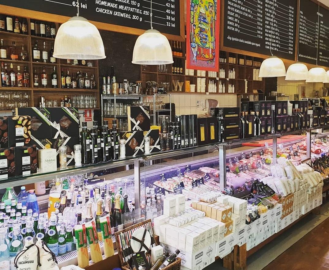 vitrina din bacania vacamuu, plina cu produse alimentare, corpuri de iluminat suspendate deasupra si in spate rafuturi cu vinuri