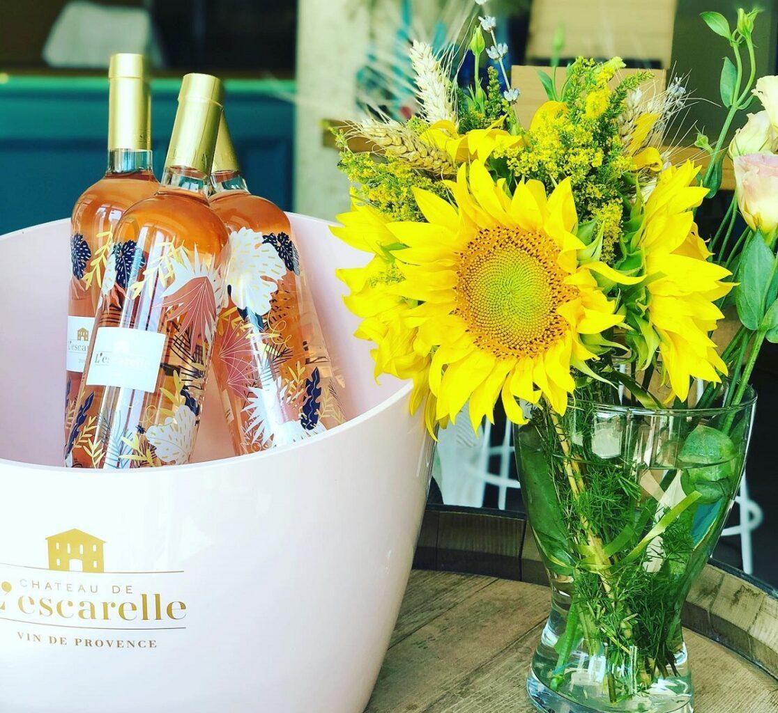sticle cu vin rose in frapeiera, langa o vaza cu floarea soarelui, la wine ambassador bucurești