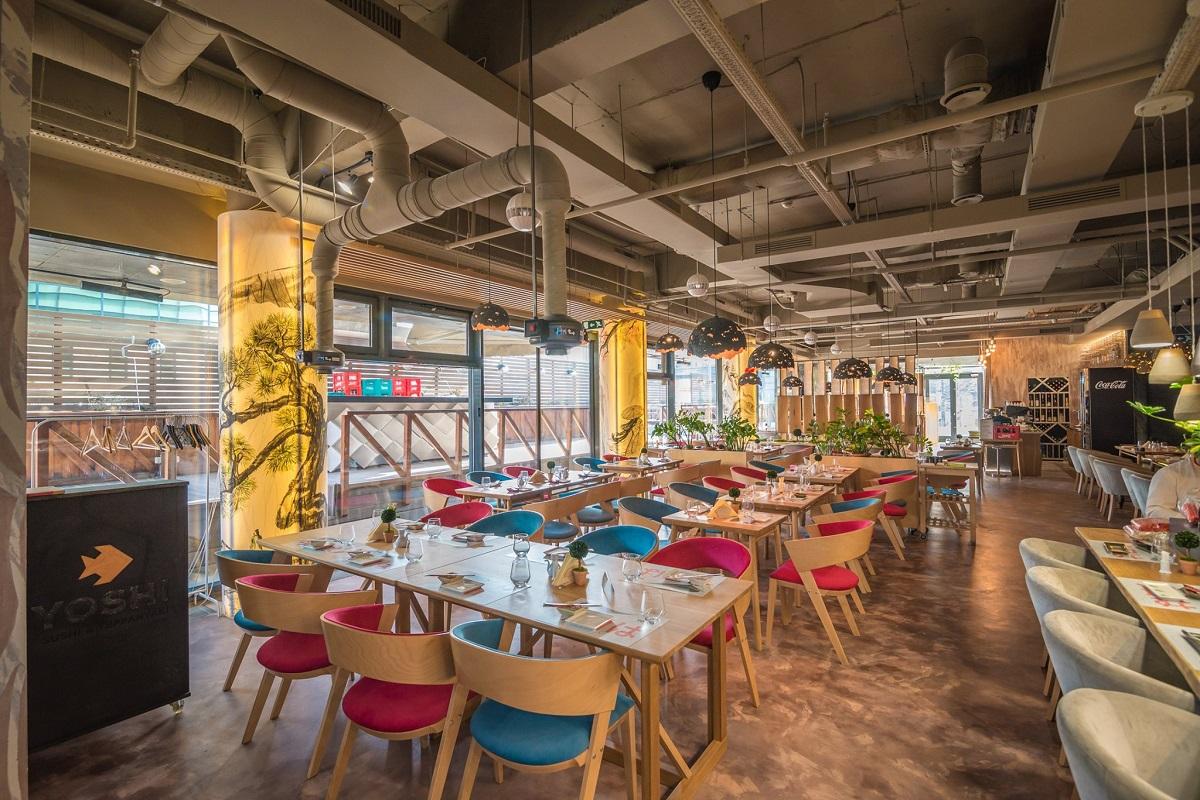 imagine de ansamblu din interiorul restaurantului Yoshi Sushi, cu mese de lemn si scaune tapitate in rosu si albastru, cu tavan industrial