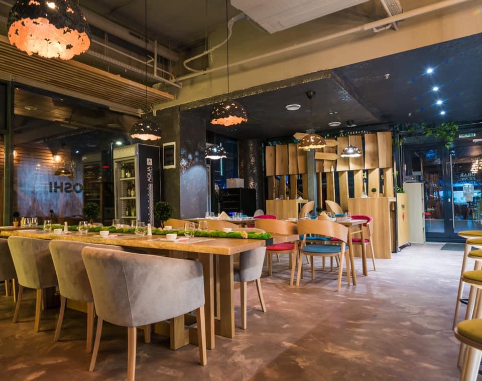 mese de restaurant, cu scaune cu spatar rotunjit, capitonate, si pereti negri, la yoshi sushi bucuresti