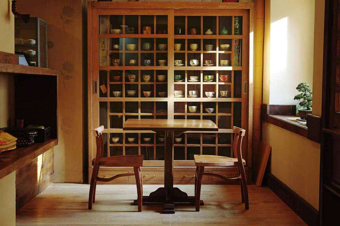 o masa cu doua scaune in fata unui dulap cu rafturi mici si multe, din lemn, la restaurant japonez Yuki