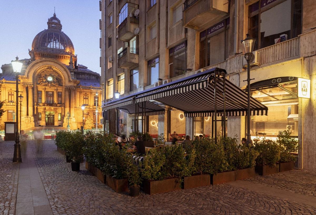terasa restaurantului Le Bab din București, fotografiata seara, imprejmuita de ghivece cu gard viu si acoperita cu copertina de panza alb si negru, una din terase pet friendly din București