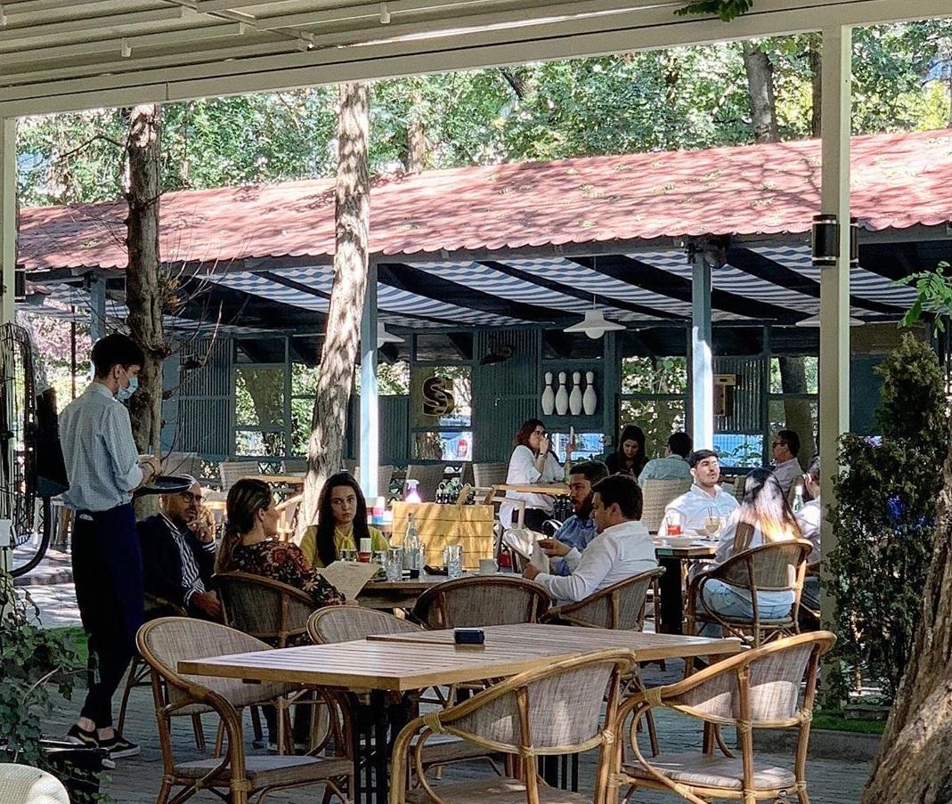 oameni la masa la terasa Stadio Park, cu copaci si verdeata si acoperis la mese