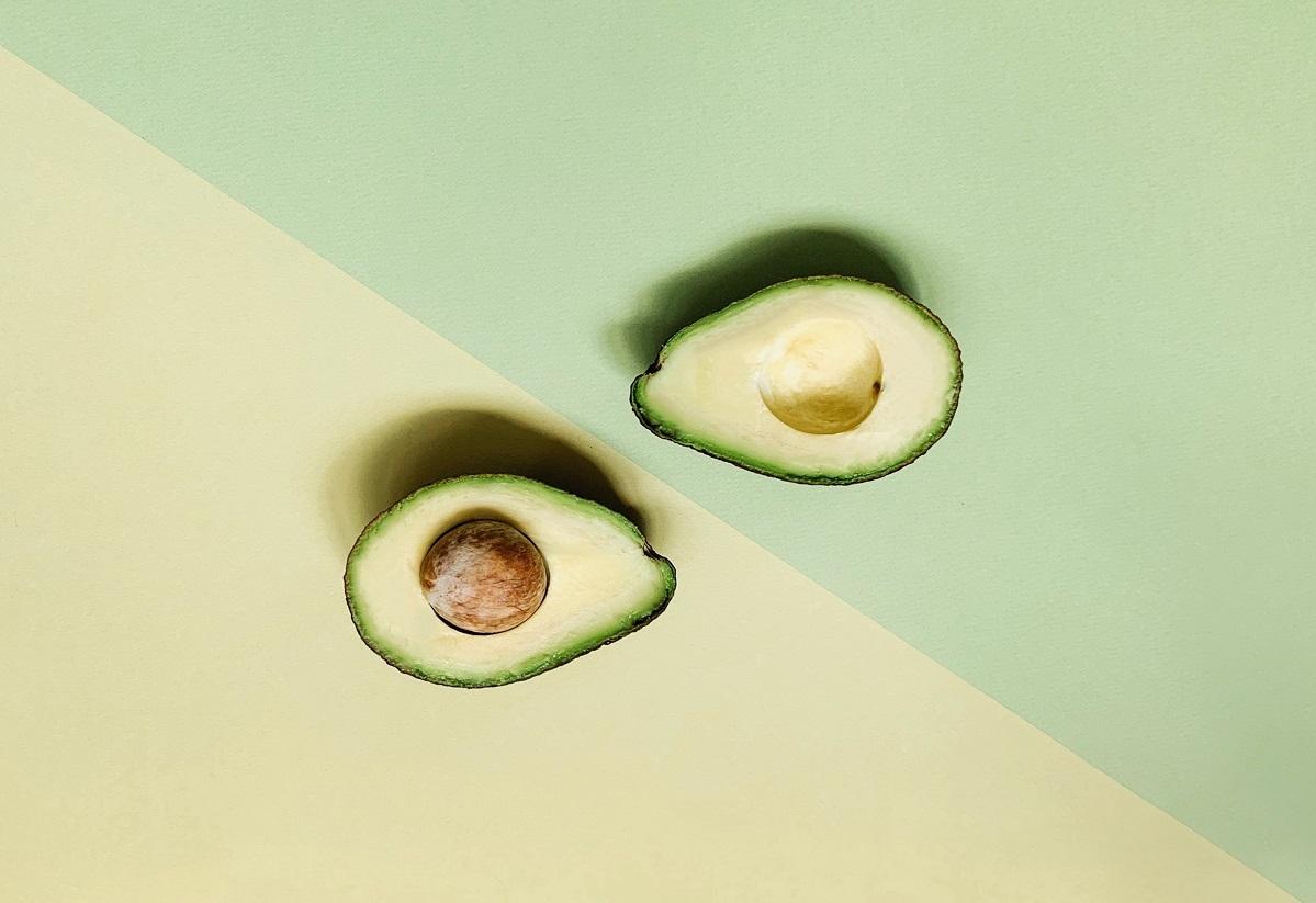 doua jumatati de avocado, una cu sambure, pe fundal crem si verde, aliment din dieta keto