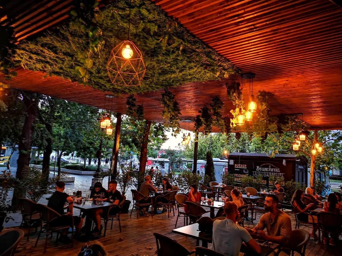 terasa de la colonial lounge bucuresti, ftografiata noaptea, cu oameni la masa, cu acoperis din lemn si corpuri de iluminat suspendate