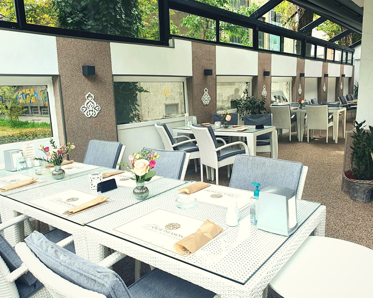 mese si scaune albe pe terasa acoperita de la four seasons dorobanți, cu pereti crem si acoperis din sticla