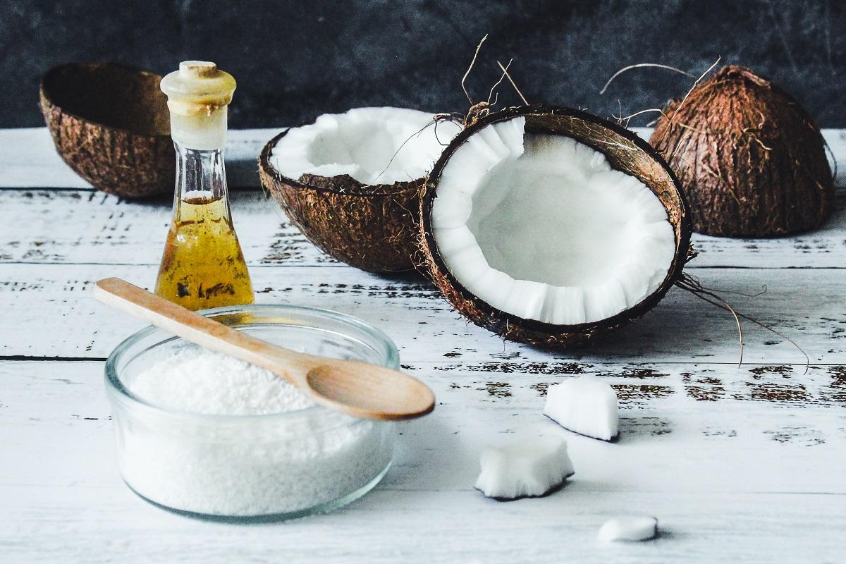 nuci de cocos despicate in doua alaturei de ulei de cocos si zahar de cocos, pe o fata de masa alba