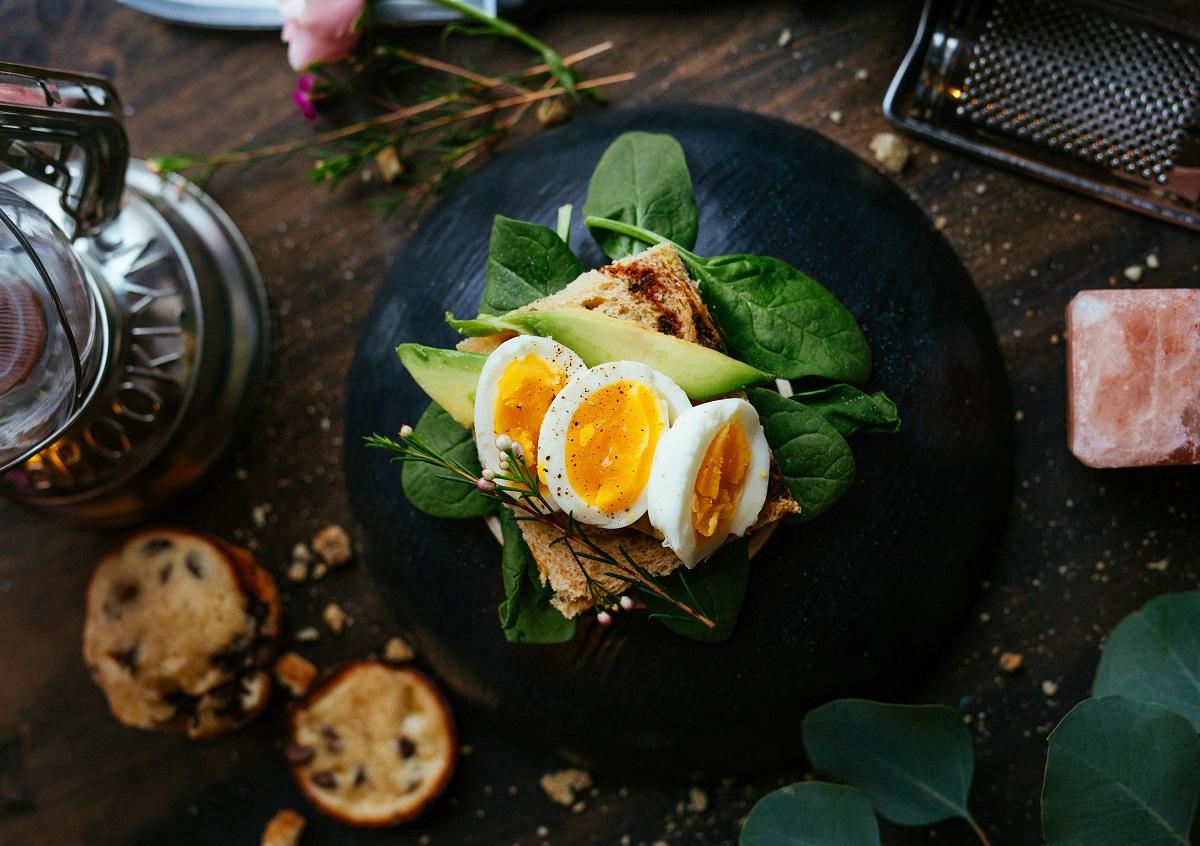 oua fierte asezate peste frunze de salata intr-o farfurie neagra, pe fundal maro inchis