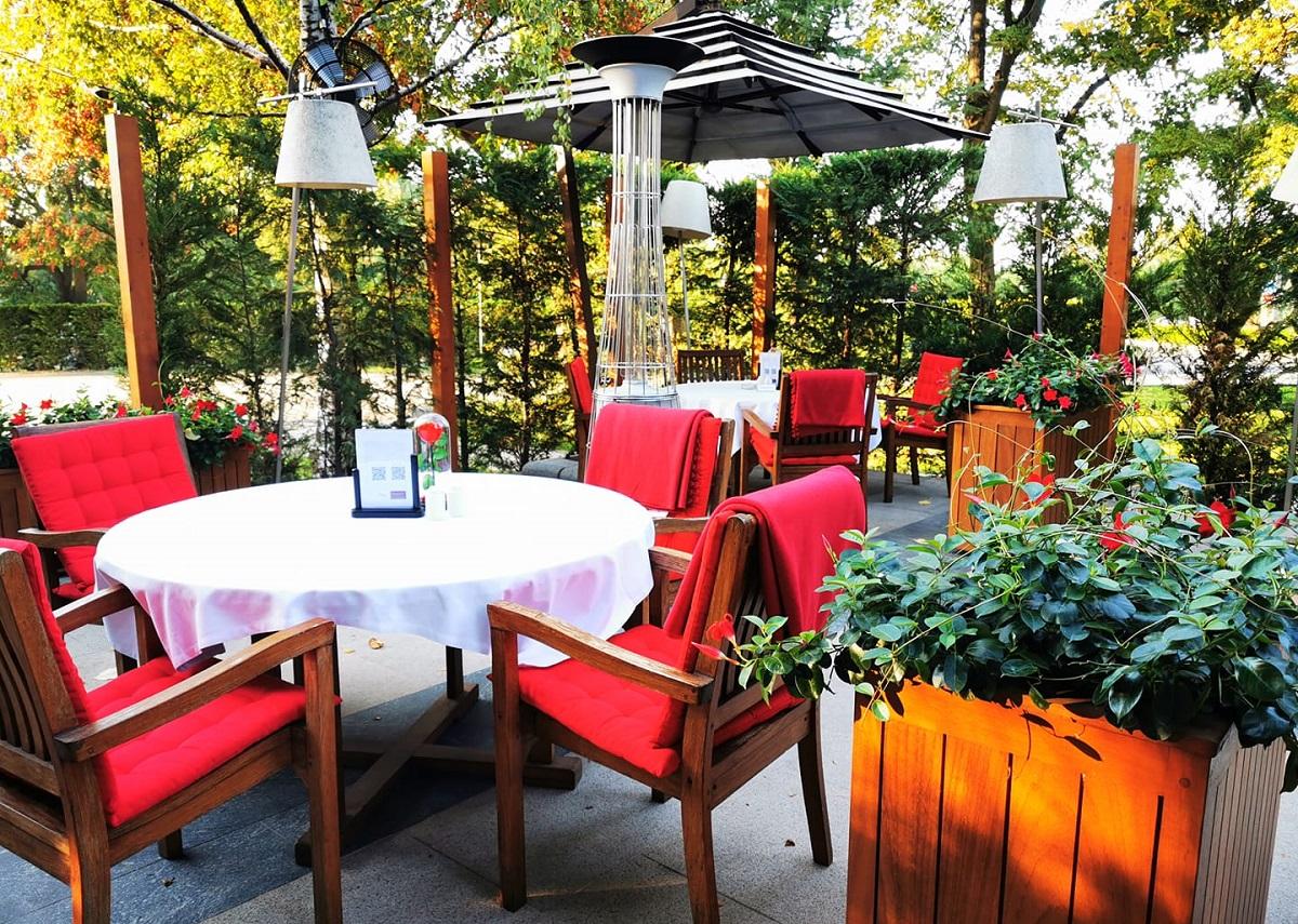 terasa in aer liber cu mese rotunde si scaune tapitate cu rosu, cu paturi pe ele, cu incalzitoare pe terasa