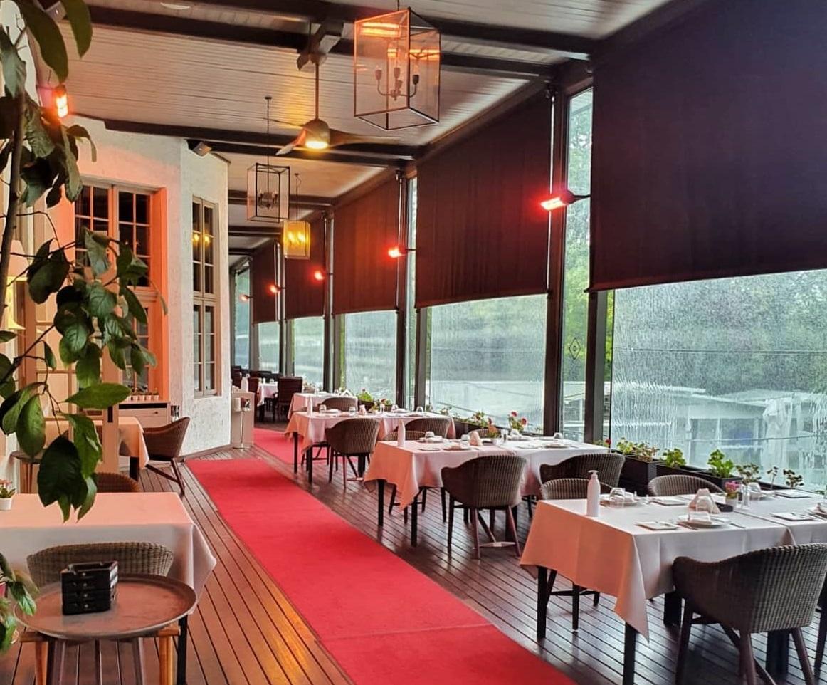 terasa restaurant diplomat din bucurești, acoperita, cu covor rosu si mese cu fete de masa albe, terasa inchisa cu copertina din plastic iar afara ploua