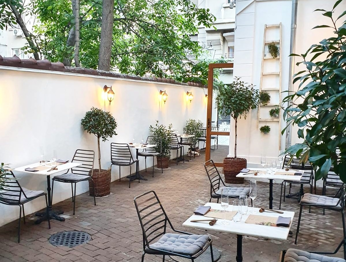 terasa anika restaurant din bucureti, cu scaune din fier forjat si mese albe, asezata pe teresa din curtea unei case albe, cu lumini pe gard