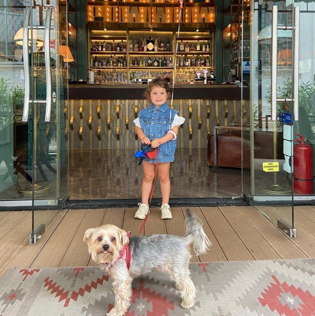 o fetita si cainele sau, la intrarea in restaurant Pow Wow București, una din terase pet friendly București