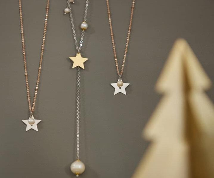 bijuterii alexandra caspruf, cu stelute si in prim plan, blurat, un ornament in forma de brad auriu, pentru cadouri de crăciun