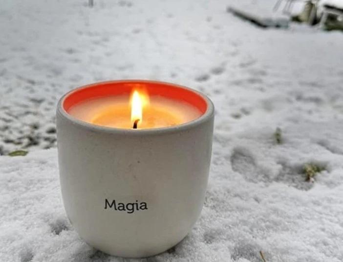 """cana din portelan  pe care este scris """"magia"""" cu lumanare aprinsa asezata pe zapada, de la cup&candle by Oana Botezatu"""