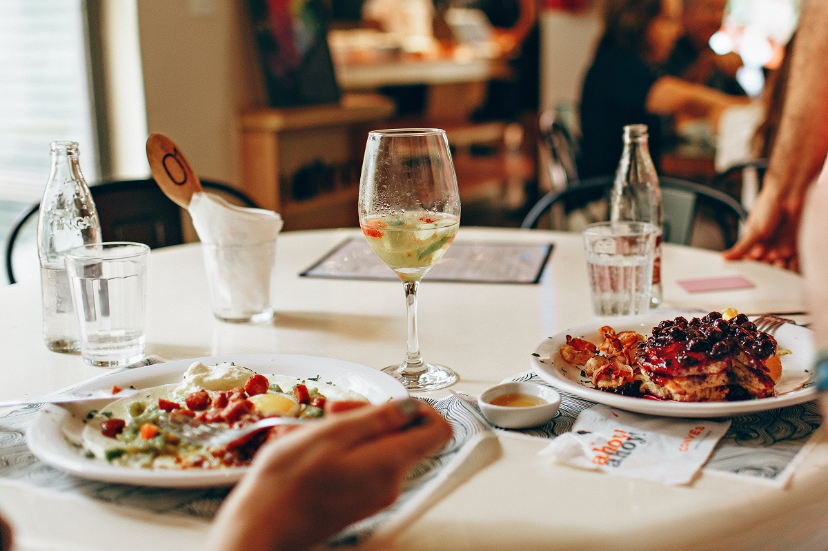 close up cu doua farfurii cu mancare asezate pe masa si un pahar de bautura in mijloc, doi oameni luan masa la restaurant