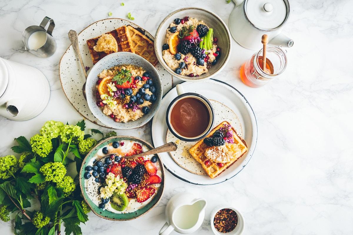 farfurii fotografiate de sus cu preparate de mic dejun cu vafe, cereale cu fructe cafea si suc, ca tențe culinare 2021