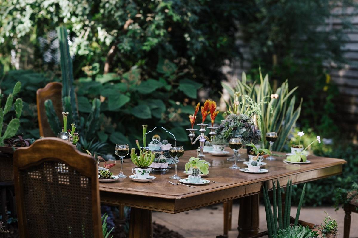 masa din lemn cu ghivece mici de plante si pahare de vin, inconjurata de plante, de la un restaurant de destinatie tendințe culinare 2021