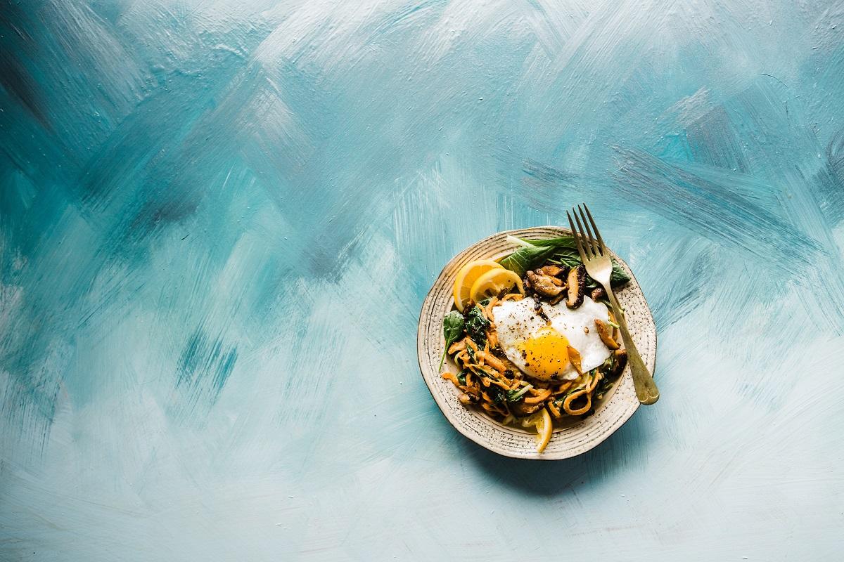 farfurie cu mancare fotografiata de sus, pe fundal albastru pictat, sugestivă pentru tendințe culinare 2021