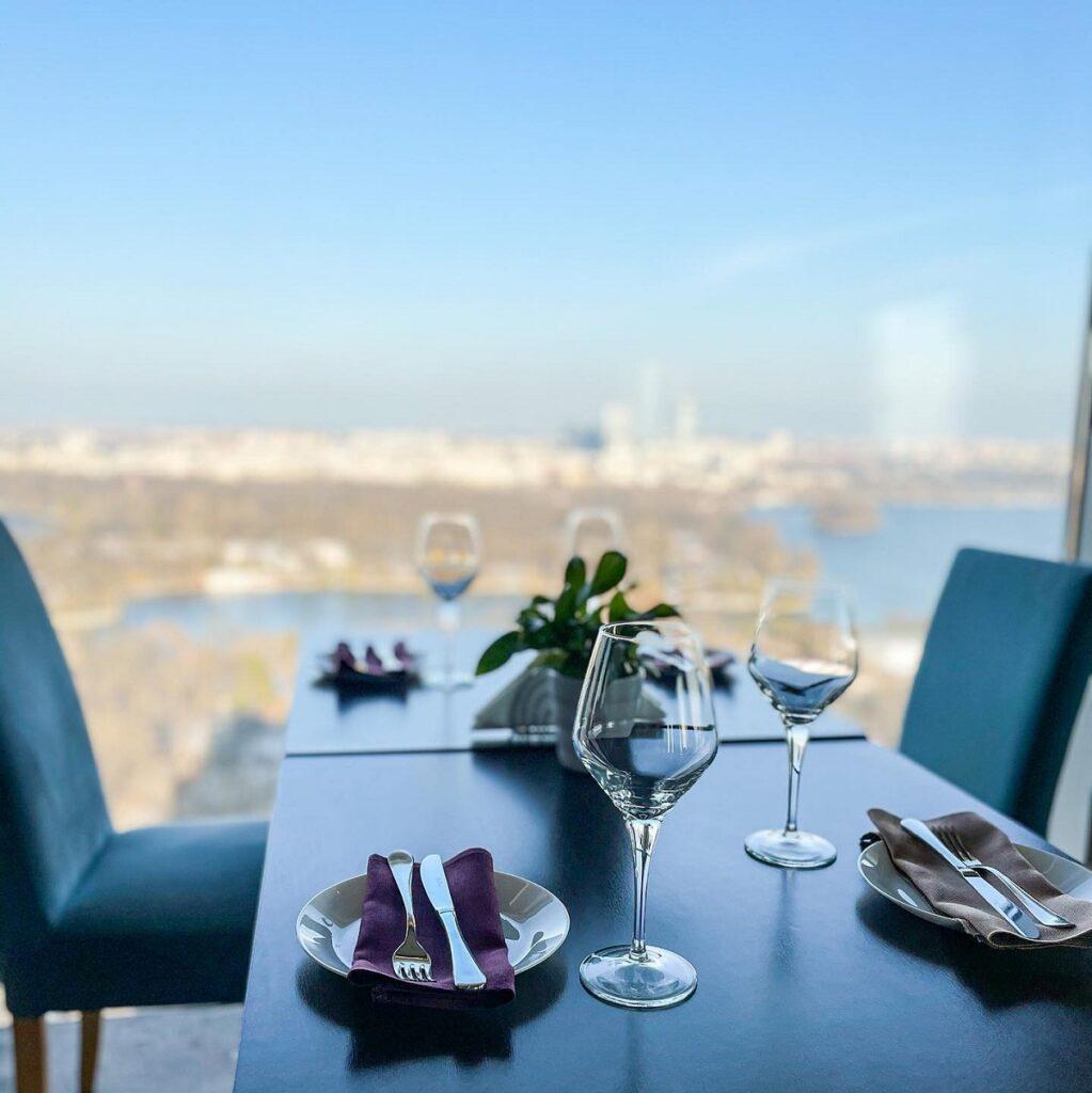 masa  asezata in fata unui geam de la care se vede panorama Bucureștiului, la terasa 18 Lounge
