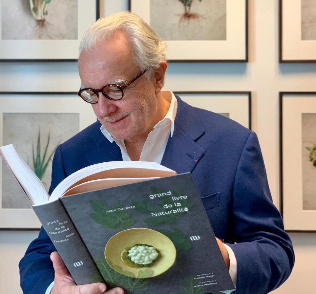 Alain Ducasse in costum albastru, citind din una din cartile sale, unul din cei mai buni bucătari din lume