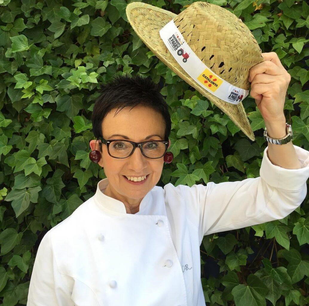 Chef Carme Ruscalleda imbracata in uniforma de bucatar, cu o palarie de soare in mana