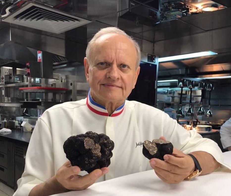 Joël Robuchon in uniforma de bucătar, cu doua trufe in mana, cel mai bun bucătar din lume